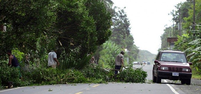 People remove a fallen tree from the road in Cienaguita